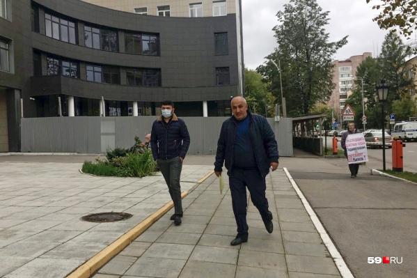 Отец и сын — он же подсудимый — подходят к зданию суда. На заднем плане — одиночный пикет женщины, требующей реального срока для подростка