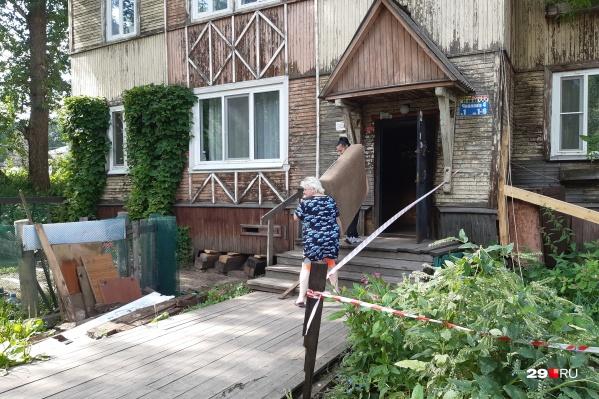 Надежда Солдатова вместе с соседкой выносит из своей квартиры диван, чтобы было на чем сидеть возле дома