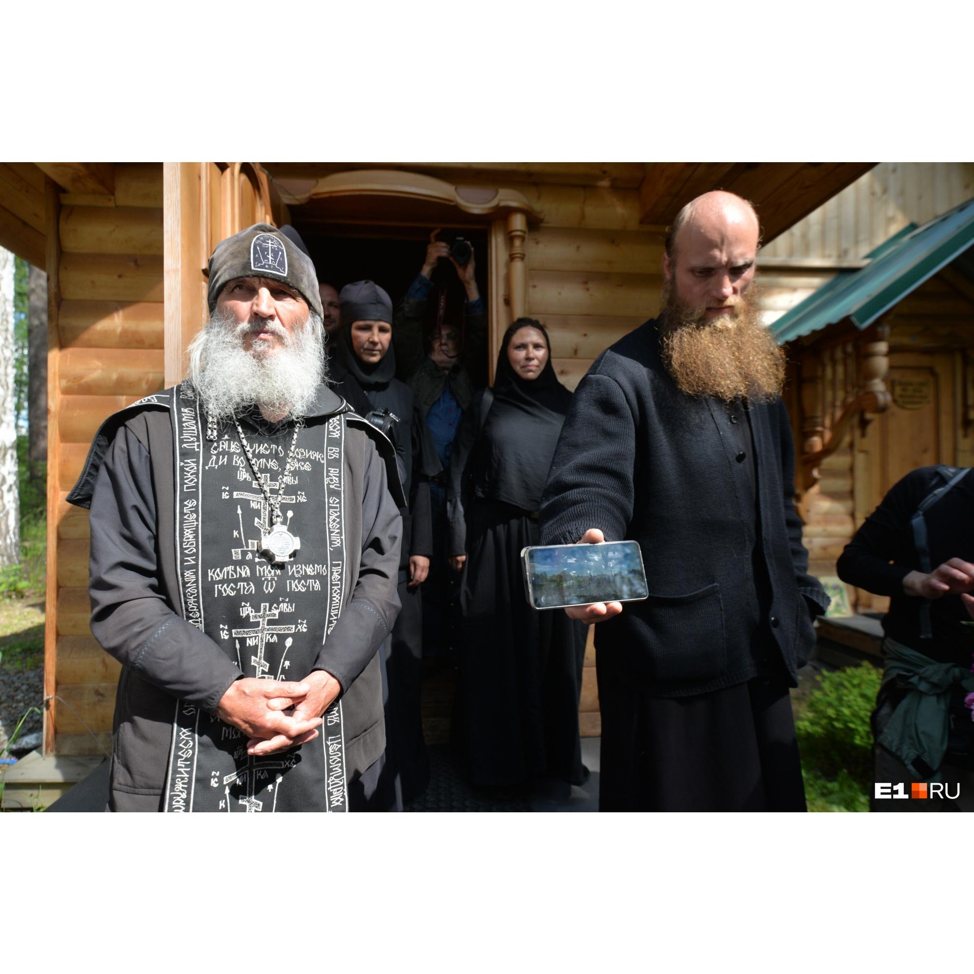 Отец Сергий у своей кельи. Внутри портреты патриарха Алексия II соседствуют с фотографиями Сталина