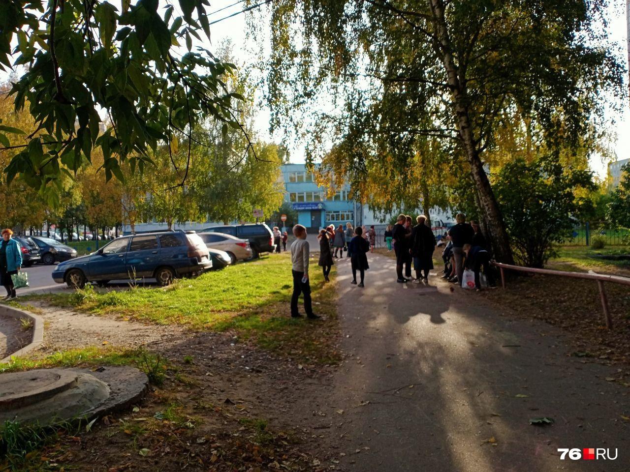 Дети и учителя гуляют около школы