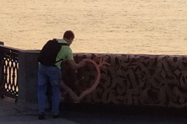 Молодой человек нарисовал сердечко на произведении уличного искусства