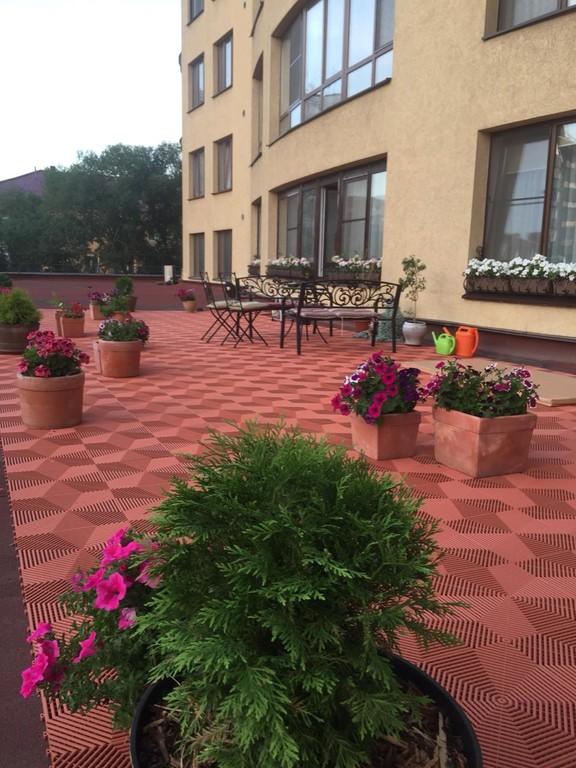 На террасе много цветов и элитной садовой мебели