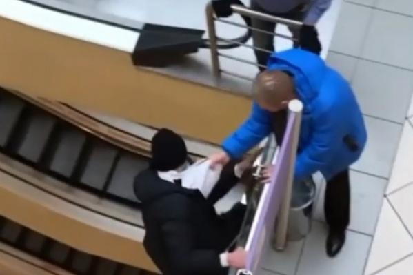 Молодой человек перелез через перила, убегая от охранника