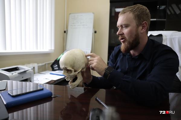 Глава тюменских судебных медицинских экспертов держит в руках череп девушки, которая «живет» у него в кабинете и даже иногда помогает ему в работе. Откуда череп — в конце интервью<br>