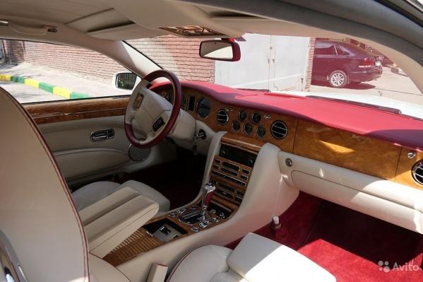 Внутри автомобиль отделан деревом, малиновой и белой кожей