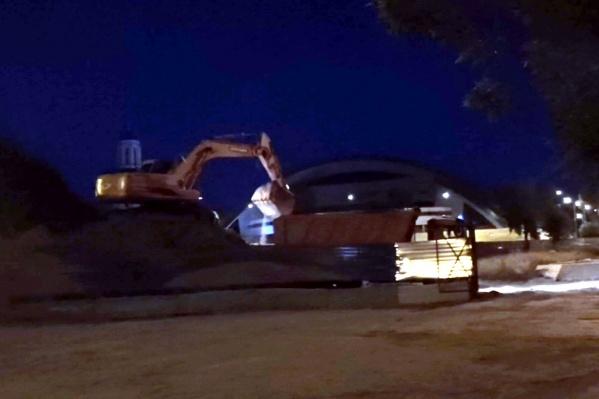 Ночью на месте строительства работают экскаватор и три самосвала