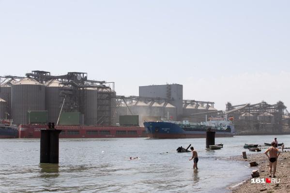 Напротив пляжа — элеватор и завод, а по реке постоянно идут корабли