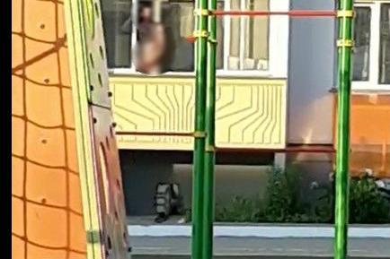 Мужчина стоял на балконе прямо напротив детской площадки