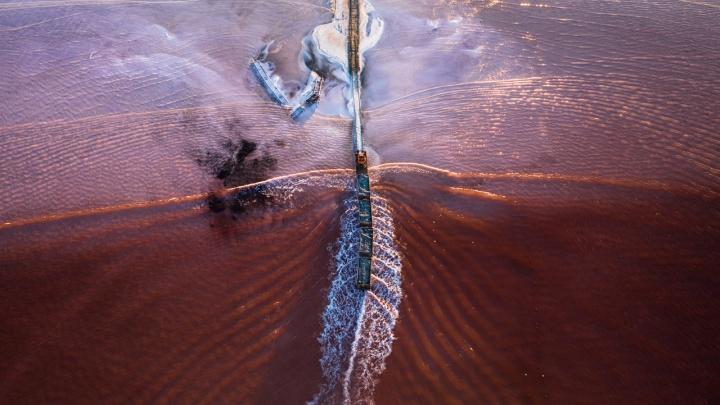 Новосибирский фотограф с высоты сделал удивительные кадры сказочного розового озера, по которому ходит поезд