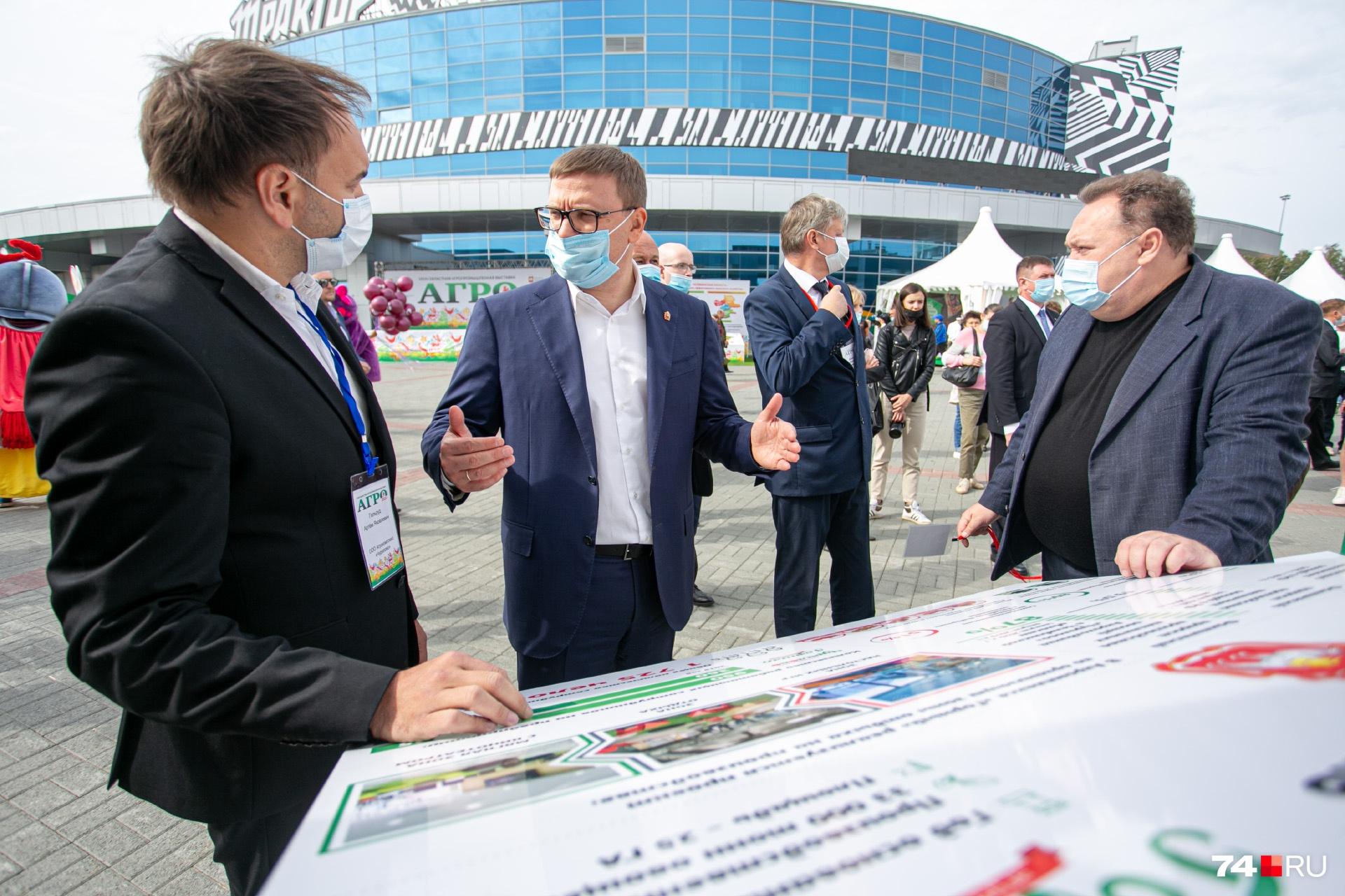 Текслер и его заместитель Сергей Сушков подошли к стенду «Чурилово» — судя по жестам, речь идёт о гигантских огурцах