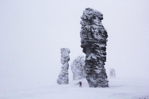 Человек кажется крошечным рядом с огромными каменными глыбами Маньпупунёр