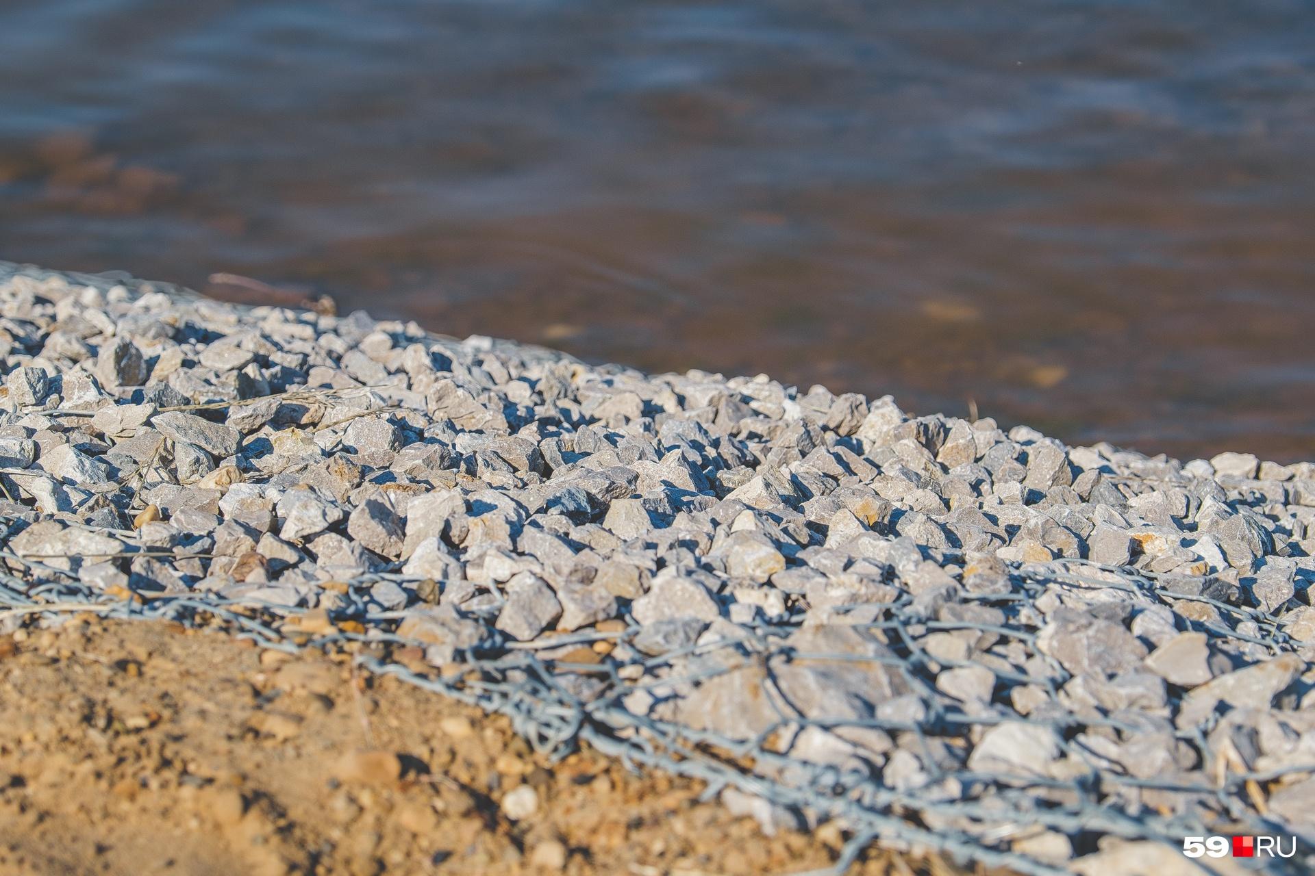 Берег укреплен сеткой и камнями
