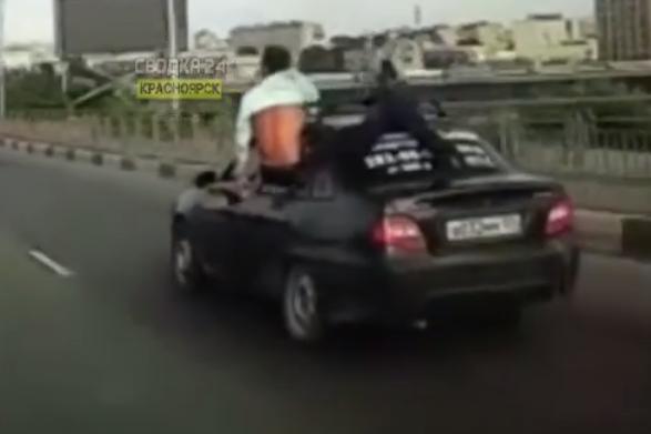 Молодой человек вылез по пояс из машины, которая была на ходу