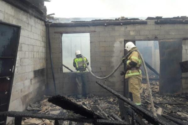 Пожарные проливают сгоревший ангар