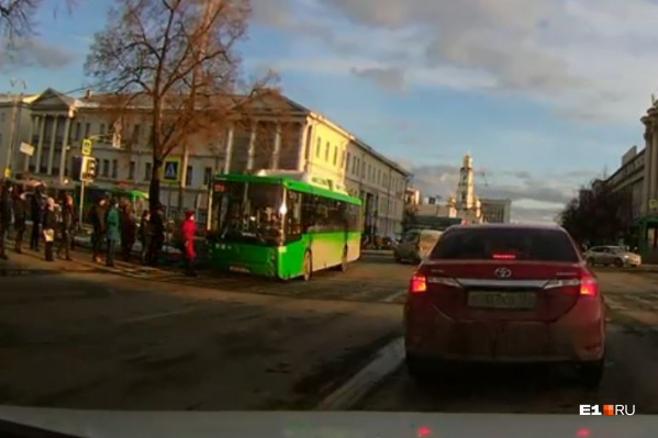 На кадрах видно, что пешеход начала движение на зеленый сигнал светофора