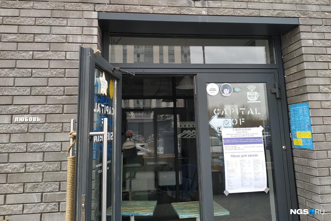 Вход в кофейню заграждён столами, бариста сам подходит к двери