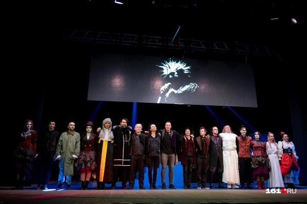 Труппа зонг-оперы с образом Михаила Горшенева на фоне