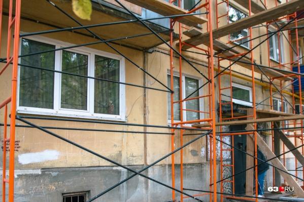Рабочий приводил в порядок фасад дома