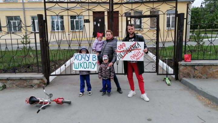 Семья из Челябинска вышла к школе с плакатами против дистанционки