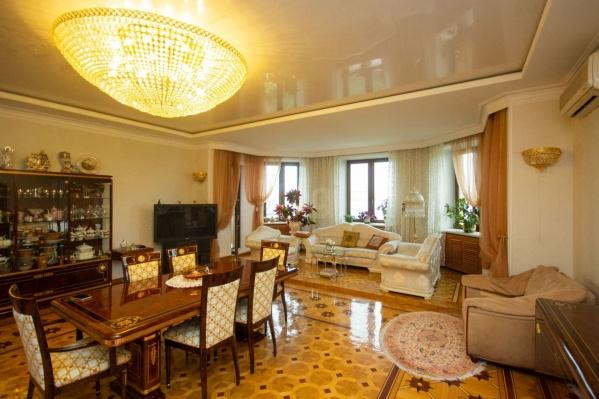 Гостиная занимает 51 квадратный метр, освещается огромной итальянской люстрой