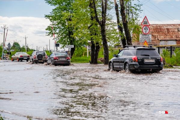 Участок дороги у переезда в конце мая затопило