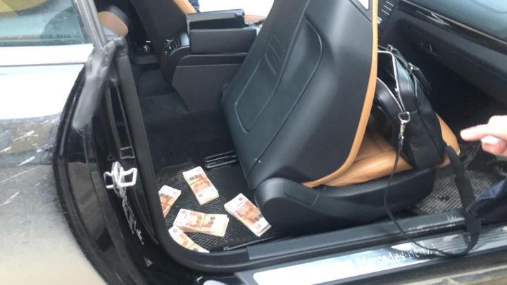 Пачки денег лежали на коврике: появилось видео задержания подозреваемого в мошенничестве полицейского