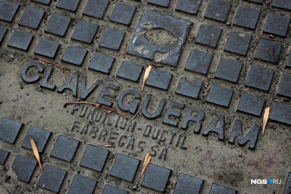 Тяжелые чугунные крышки с надписями на каталанском языке лежат на улице Урицкого уже не одно десятилетие
