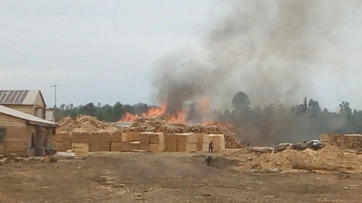 На севере Красноярского края загорелась лесопилка со штабелями леса