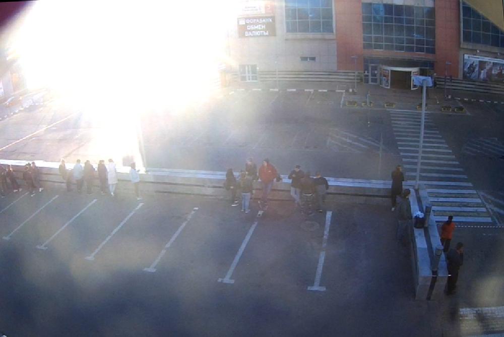 Люди стоят за парковкой