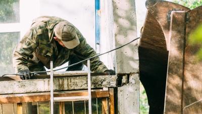 Трактор, который держал дом, или фоторепортаж о том, как в Омске плиты на место вставляли