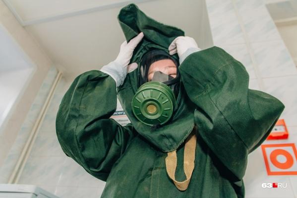 Врачи работают с зараженными в защитных костюмах