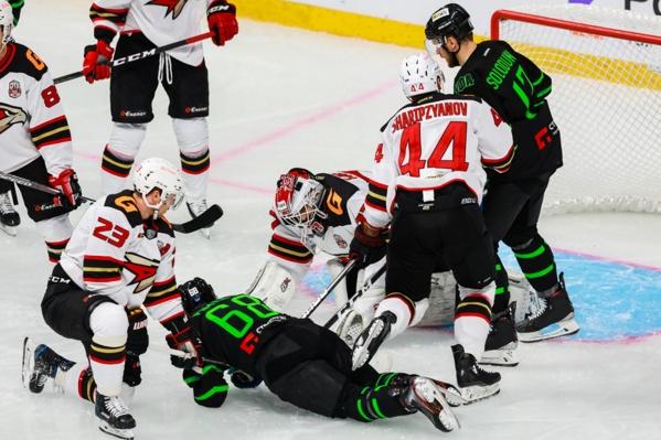 Хоккеисты смотрят на то, как нападающий «Салавата Юлаева» Артём Пименов отдыхает на льду