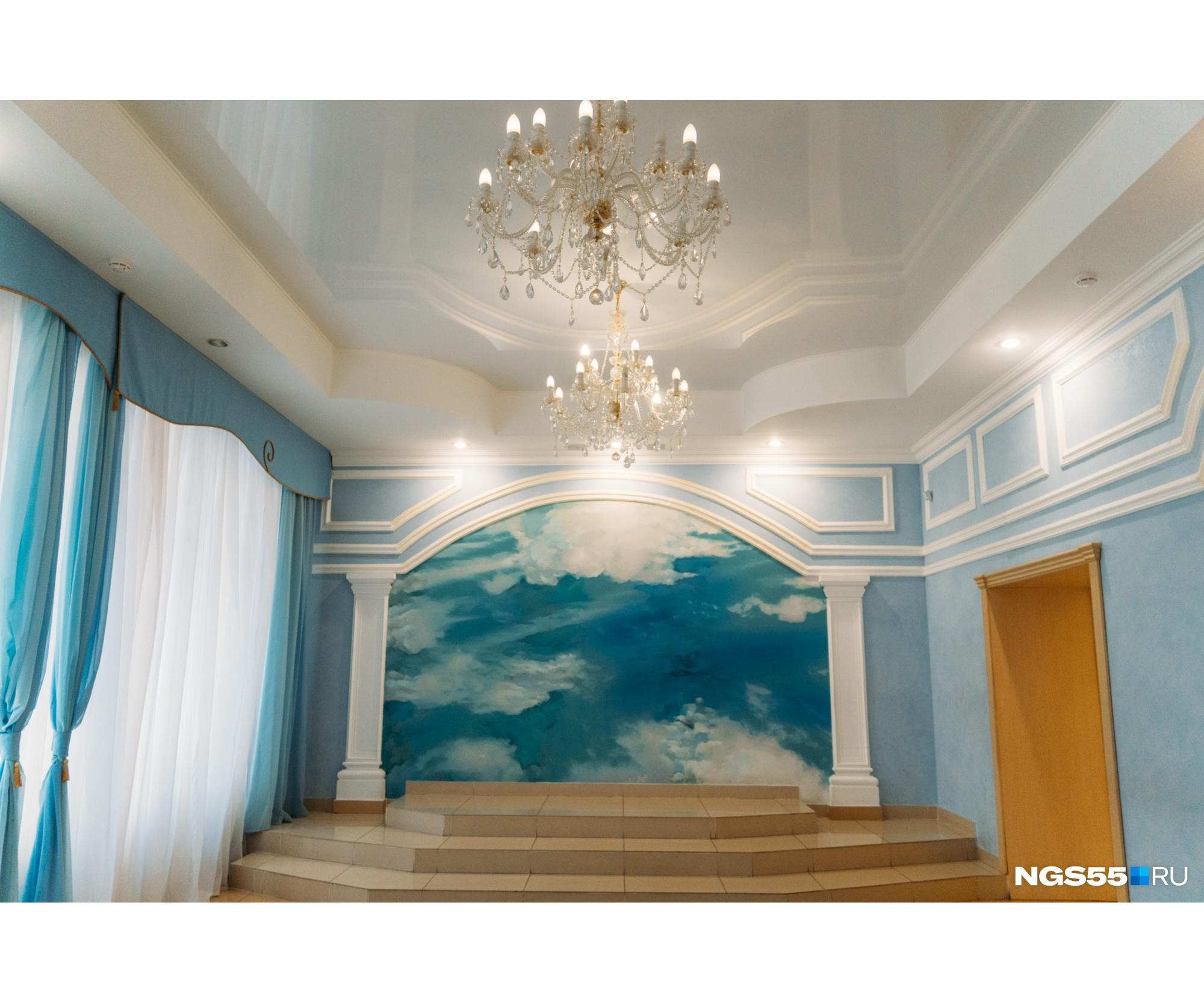 Это помещение оформили, как фотосалон. Из-за росписи стен на снимках молодожёны и их гости словно парят в облаках