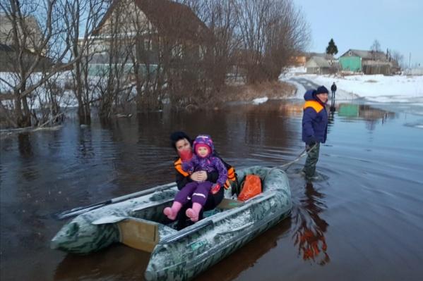 Сотрудники МЧС помогают переправиться через затопленные дороги