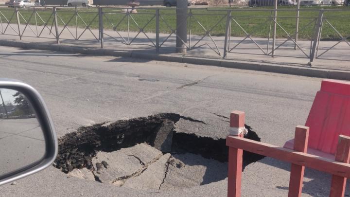 Посреди Большевистской провалился асфальт — теперь на дороге огромная яма