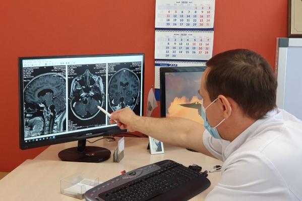 Нейрохирург показывает на снимке расположение опухоли. Подобные случаи встречаются крайне редко