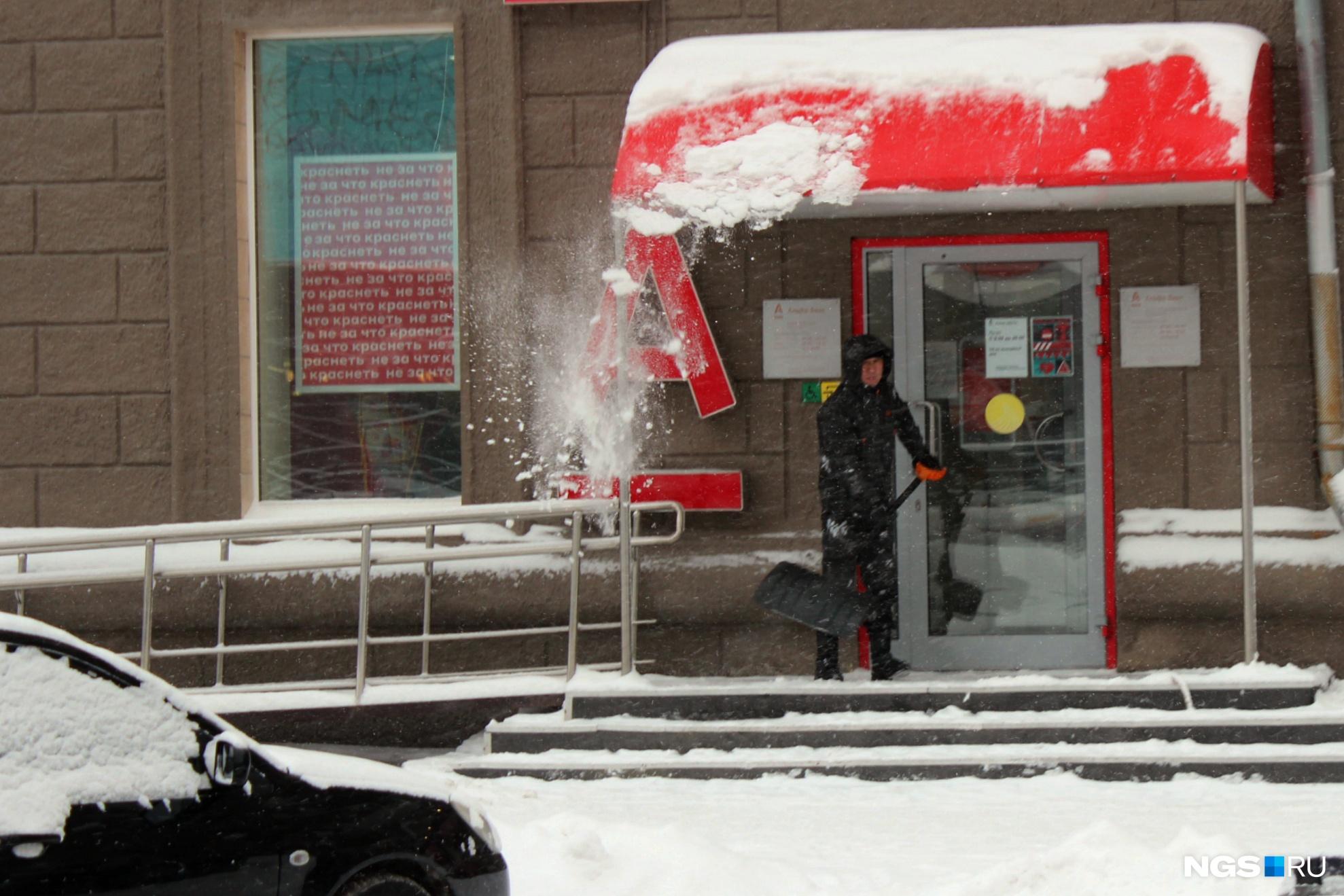 Работник чистит крыльцо и козырек отделения банка