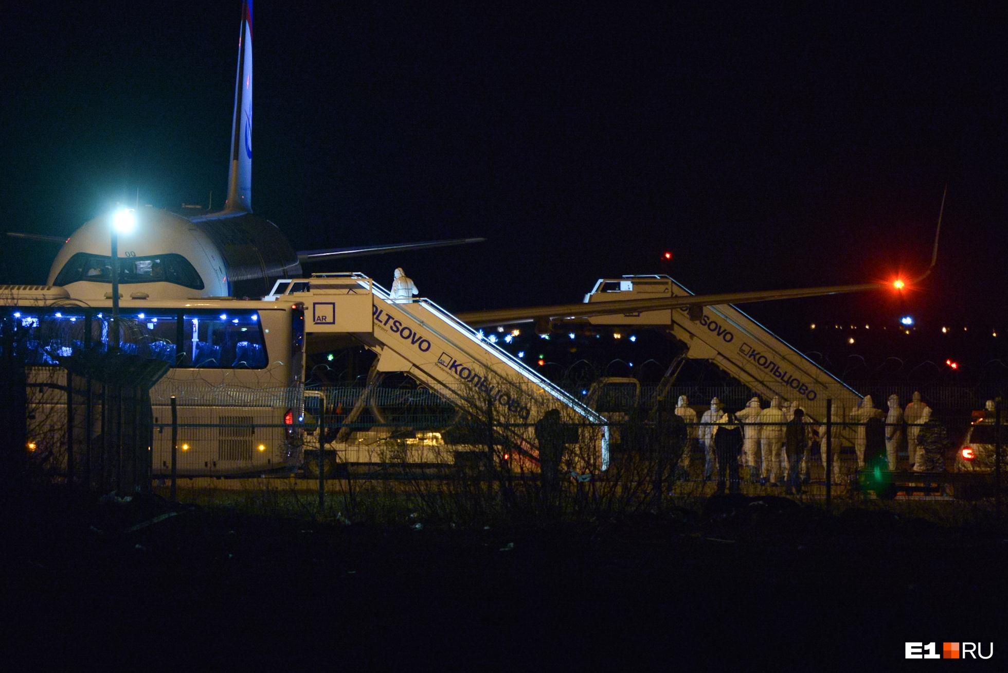 Практически сразу, как самолёт приземлился, на борт поднялись люди в защитных костюмах