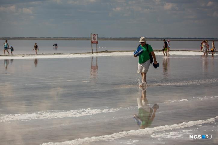 В воде стоит знак, предупреждающий о том, что по рельсам ходить нельзя. Но все ходят