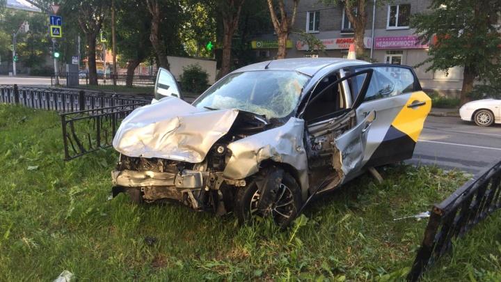 В Екатеринбурге машина такси врезалась в грузовик и пробила забор