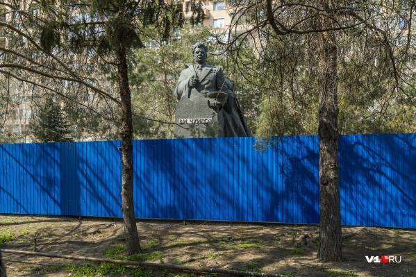 Рабочие обнесли памятник высоким забором