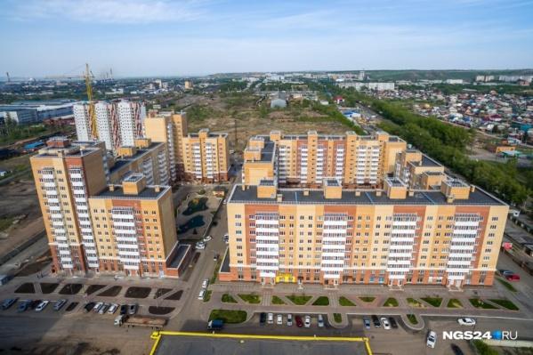 На фото позади жилых домов видно пустырь — часть его должны занять школа и садик