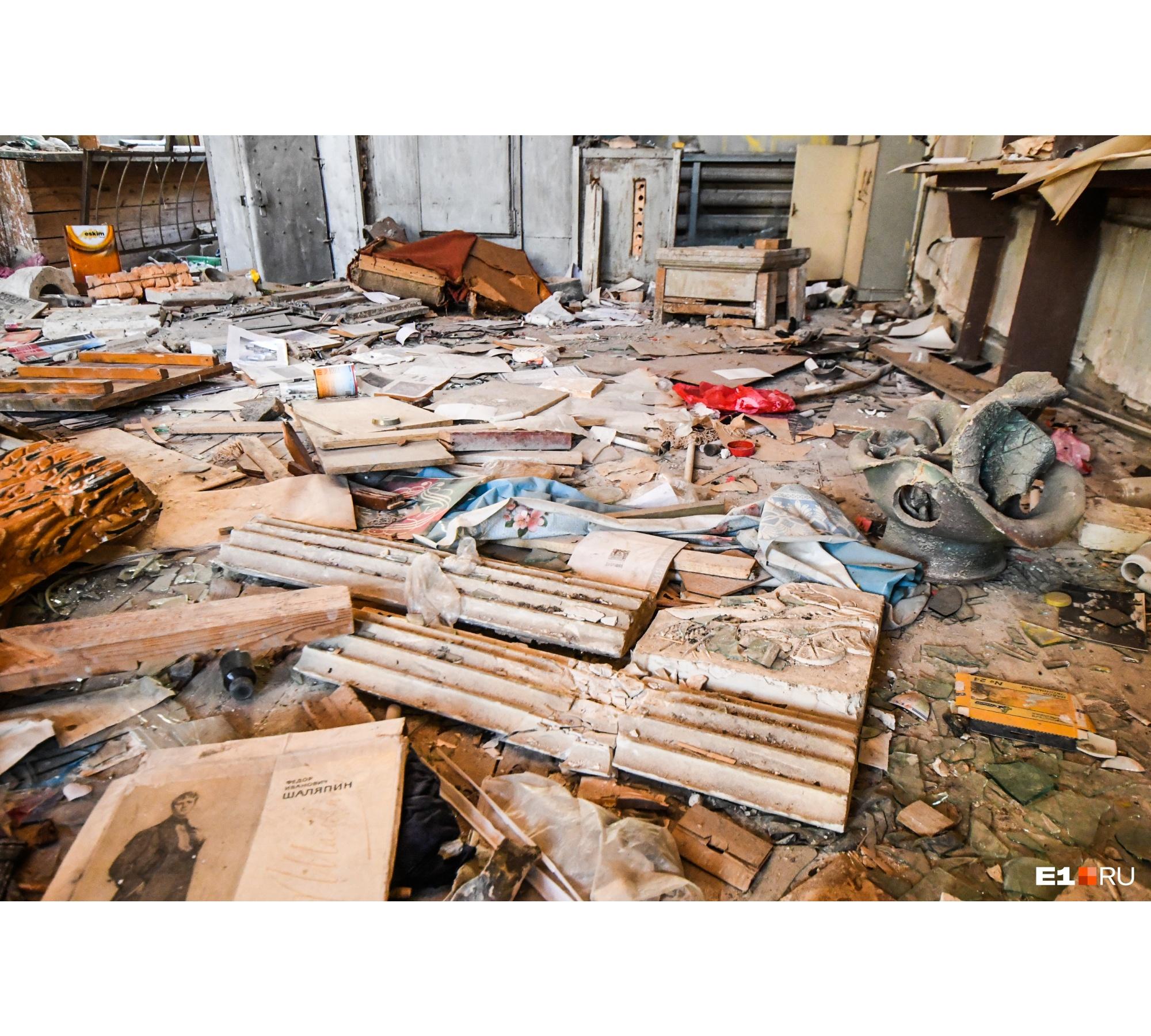 По полу разбросаны остатки художественных материалов, книг и фотографий