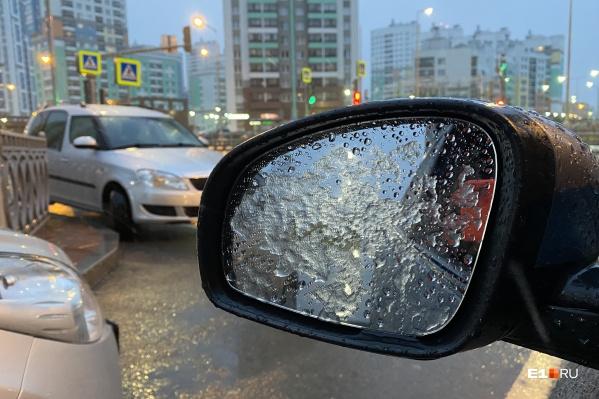 Снег налипает на стекла и зеркала машин, но быстро тает