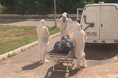Сотрудники, которые грузят умерших в специальные машины, надевают защитные костюмы