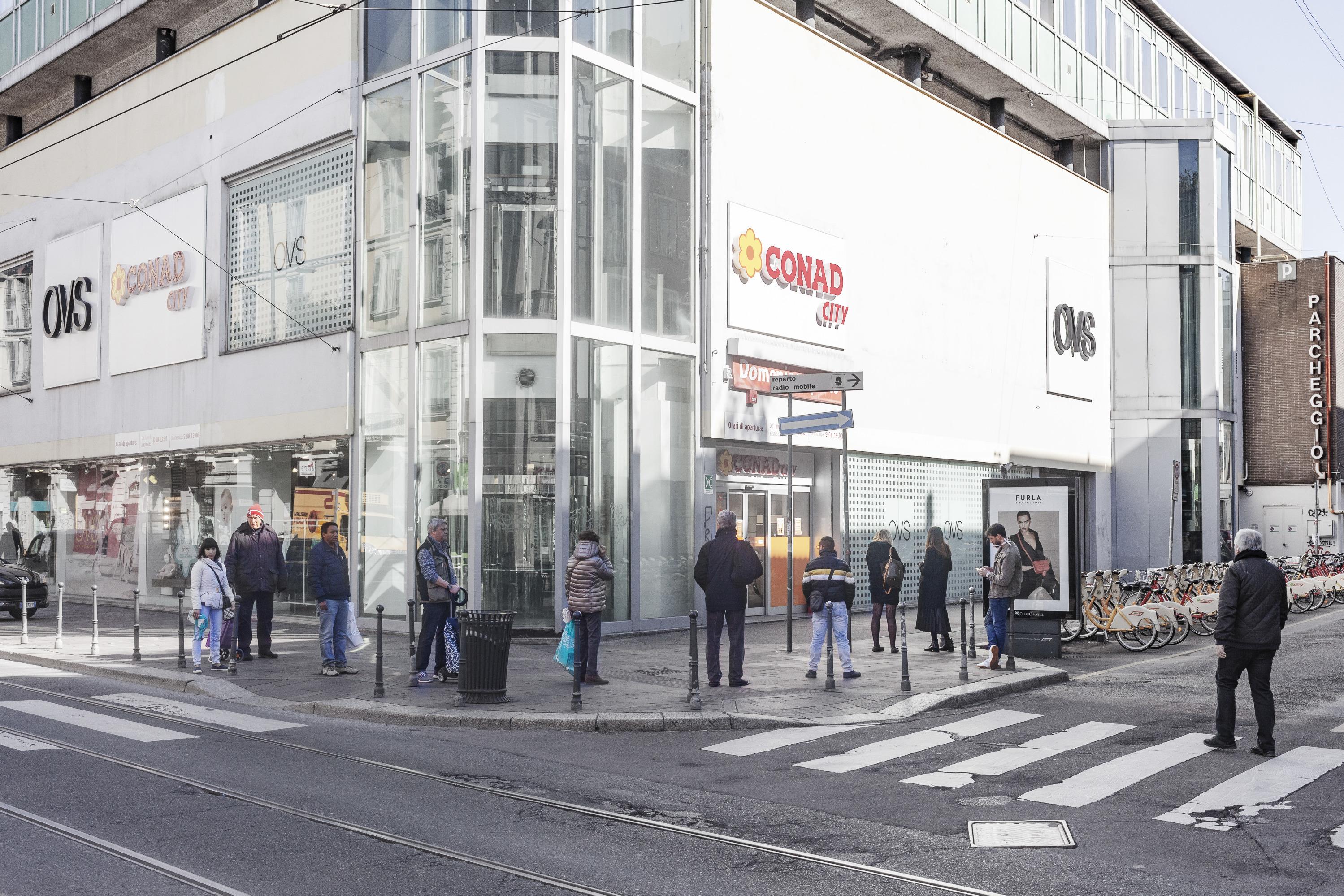 Люди стоят в очереди у супермаркета. Между каждым человеком сохраняется безопасное расстояние в один метр, и только несколько человек за один раз допускаются внутрь