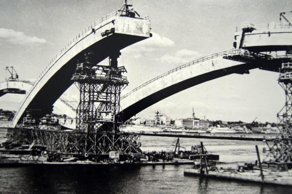 Мост был чрезвычайно необходим после эвакуации в Красноярск многих предприятий во время Великой Отечественной войны (они работали на правом берегу Енисея). Но в 1940-е все ресурсы страны были брошены на помощь фронту, поэтому мост начали строить только спустя 11 лет после победы