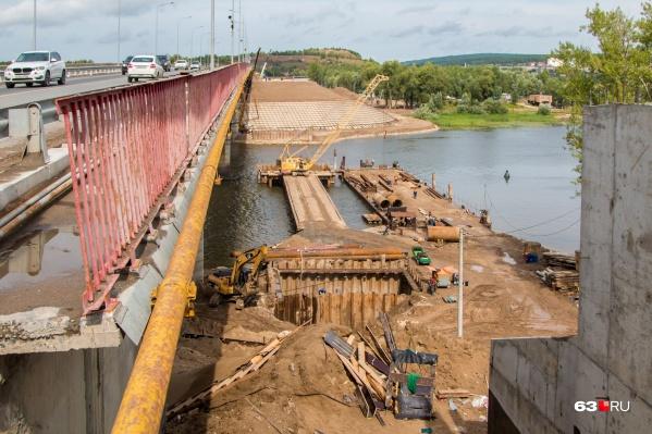К последней опоре построили мостик и подвели баржу