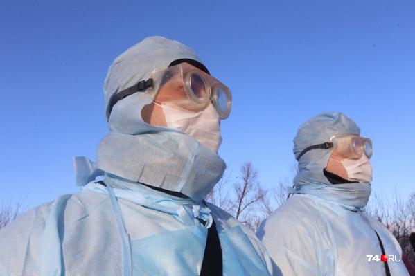 Люди в масках и специальном костюме обрабатывают общественные места (к примеру, салоны автобусов) от коронавируса
