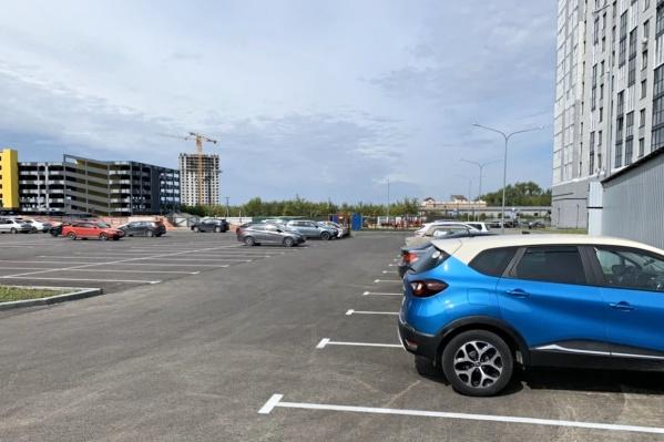 Жители и гости ЖК «Олимпия», как обычно, ставят машины на открытой парковке. Но вскоре всё может измениться